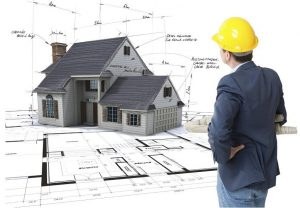 Architect looking at House mock-up on top of blueprints with pen notes and corrections